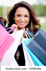 Beautiful woman shopping holding her purchases and smiling