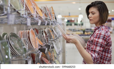 Beautiful woman shopping tableware, choosing plates in supermarket