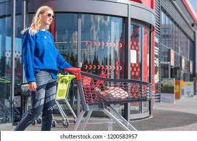 beautiful woman with shopping trolley at the door of a large store