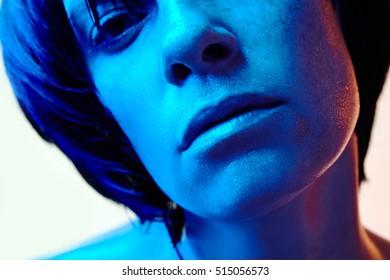 beautiful woman with short black hair and blue light closeup