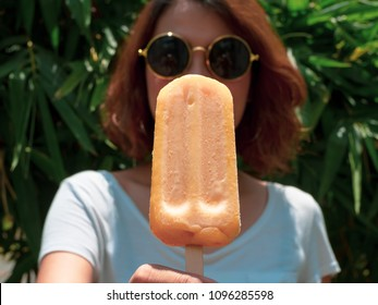Beautiful Woman Short Hair Wearing White Shirt and Round Sunglasses with Happy Smiling Holding Yellow Frozen Popsicle Ice Pop on Summer Time with Sunshine on Tree Background