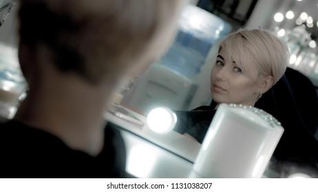 Beautiful woman with short haircut and facial piercing look at mirror at herself