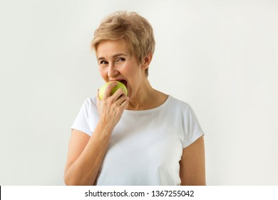 beautiful woman with a short haircut in a white t-shirt bites an apple