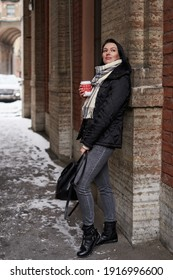 a beautiful woman with shoulder-length dark hair stands in winter clothes, leaning her back on a stone wall and holding a red disposable cup in her hands