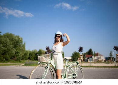 Beautiful woman show the helmet on her head during cycling. Cycling safety concept.
