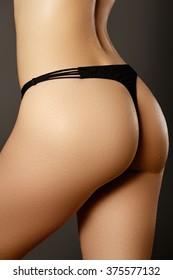Beautiful woman show her tan slim body. Beautiful slim woman body. Sexy  woman in black lingerie. Beautiful body of woman exposing bottom and back side. Perfect shining skin for summer