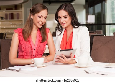 Beautiful woman showing her friend photos on tablet. Sharing memories from the trip or event