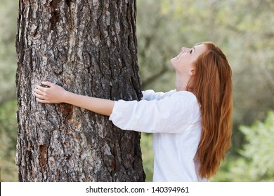 Beautiful woman showing her love of nature standing with her arms around the trunk of a tree looking up into the canopy with a lovely smile