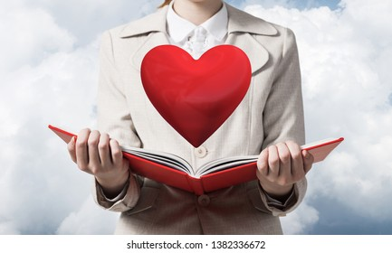 Beautiful woman showing red heart above opened notebook. Love and tenderness, valentines holiday and fall in love concept. Close up woman hands holding open book on background of skyscape.