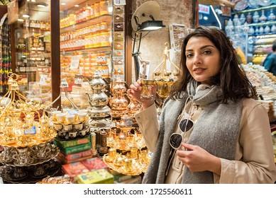 Beautiful woman shows traditional Turkish Tea glass sold a shop in Egypt Bazaar in Eminonu,Istanbul,Turkey