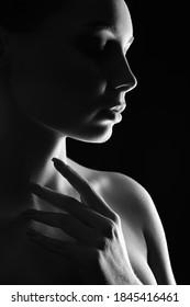 Schöne Frauensilhouette im Dunkeln. Hübsches Mädchen. Schwarz-Weiß-Porträt