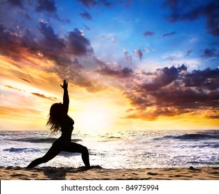 Beautiful Woman silhouette doing virabhadrasana I warrior pose on the sand beach and ocean nearby at sunset background in India, Goa