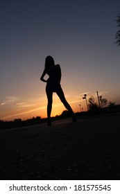 Beautiful woman silhouette posing at lake sunset.
