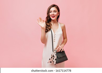 Beautiful woman in silk sundress waving her hand and posing with crossbody bag on pink background