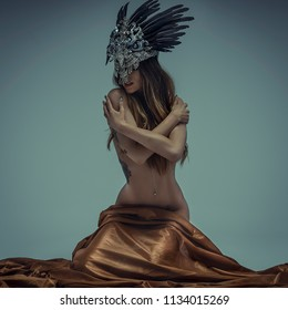 beautiful woman with silver headdress sitting on brown fabric, image of mystery and sensuality