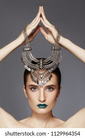 Beautiful Woman with Silver Necklace in hand over head. Modern Indian Fashion Style. Jewelry Luxury Accessories. Bright Makeup