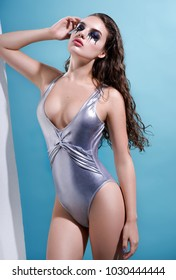 Beautiful woman in silver swimsuit and aggressive make up posing at camera