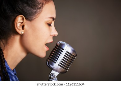 Beautiful woman singing holding retro microphone.