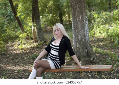 the beautiful woman sits on a bench in autumn park, an image subject the woman and the beautiful nature, seasons