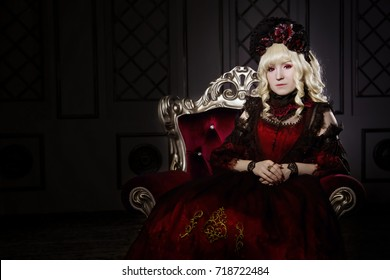 A beautiful woman sits on a carved chair, in a lush, red, gothic dress, with her hands clasped. japanese style lolita, cosplay cute. Street fashion. A vampire in a rococo manner. Your text is not