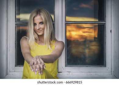 A beautiful woman sits on the window sill outdoors, in the background there is a glimmer of sunset.