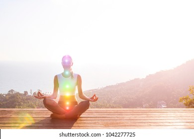 Beautiful woman sits in a pose of a half lotus on high place amazing view of the island outside, she practicing yoga meditation glowing seven all chakra eyes closed calm. Kundalini energy