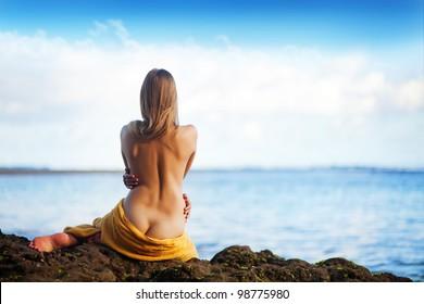 beautiful woman sitting from the back on beach, bali