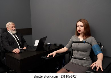 Beautiful woman sitting in black chair with sensors on fingers, hands and body of lie detector. Elderly man in black suit sitting at table and looking at computer polygraph, testing woman.