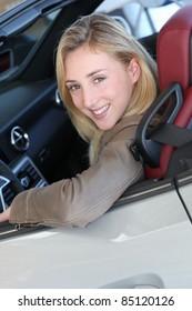 Beautiful woman sitting in brand new car