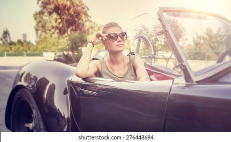 Beautiful woman sitting in cabriolet, sexy female enjoying trip on luxury modern car with open roof, fashionable lifestyle concept