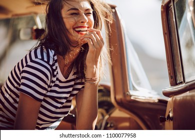 Beautiful woman sitting in a car and laughing. Woman having fun outdoors on the road trip.