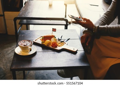 A beautiful woman sitting with coffee and  sweets and smartphone in hand at cafe recreation.