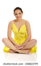 Beautiful woman sitting cross legged in yellow summer dress.