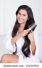 Beautiful woman sitting in a fresh white robe brushing her long straight brunette hair