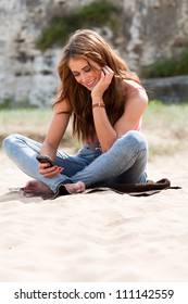 Beautiful woman sitting on beach towel holding phone texting