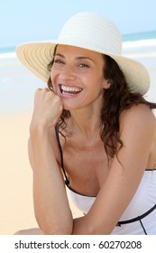 Beautiful woman sitting on the beach with straw hat
