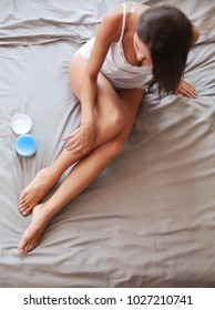 Beautiful woman sitting on bed and applying cream on legs