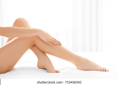 Beautiful woman sitting on bed in room