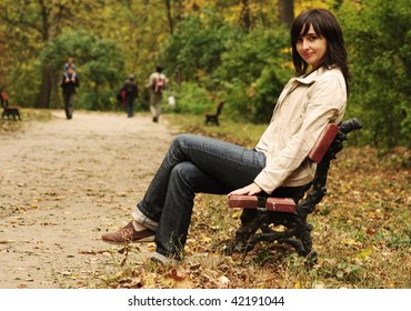 Beautiful woman sitting on the bench in the park