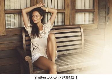 Beautiful woman sitting on the bench beside wooden house
