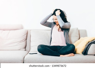 beautiful woman sitting on couch angry and frustrated shouting and tearing off hair while looking at the mobile phone - stress, communication problems and anger concept