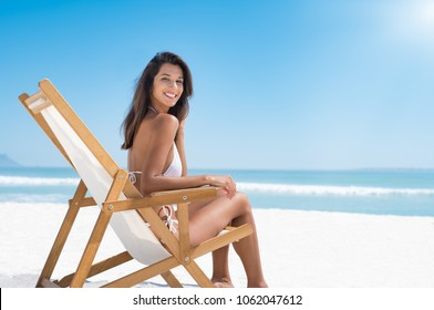 Beautiful woman sitting on a deck chair at the beach and looking at camera. Young woman in white bikini enjoying the summer with copy space. Hispanic woman subathing at seaside.