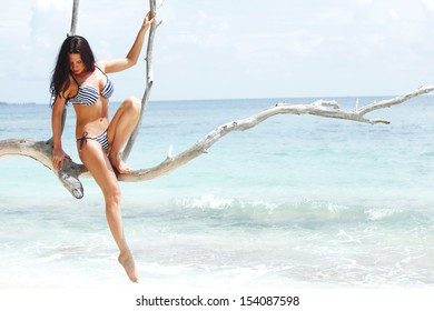 Beautiful woman sitting on dry tree near sea