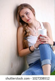 Beautiful woman sitting on the floor and holding a cup. Beautiful woman