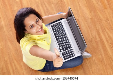 Beautiful woman sitting on the floor showing thumbs up with laptop at home