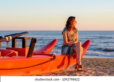 beautiful woman sitting on lifeboat by the sea on the tyrrhenian tuscan coast colorful clothing with other heels and sunglasses