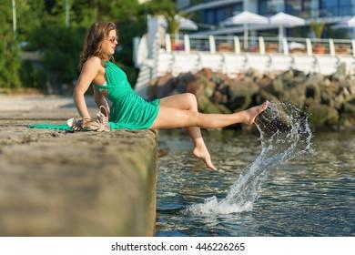 Beautiful woman sitting on the pier