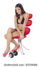 Beautiful woman sitting on red chair and training with dumbbells