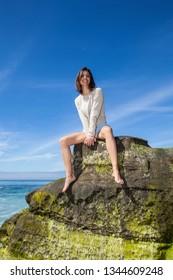 beautiful woman sitting on a rock seaside
