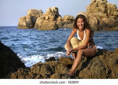 Beautiful woman sitting on a rock
